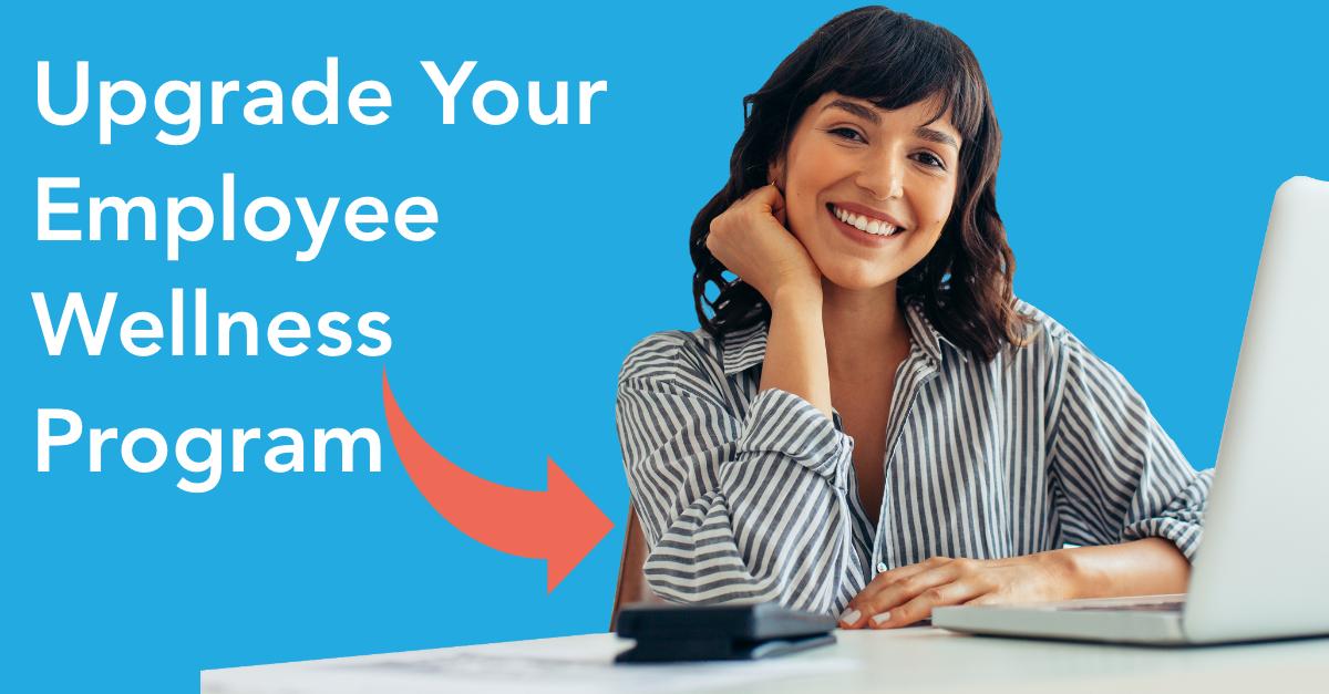 Female employee smiling at desk. Employee Wellness Programs need updating!
